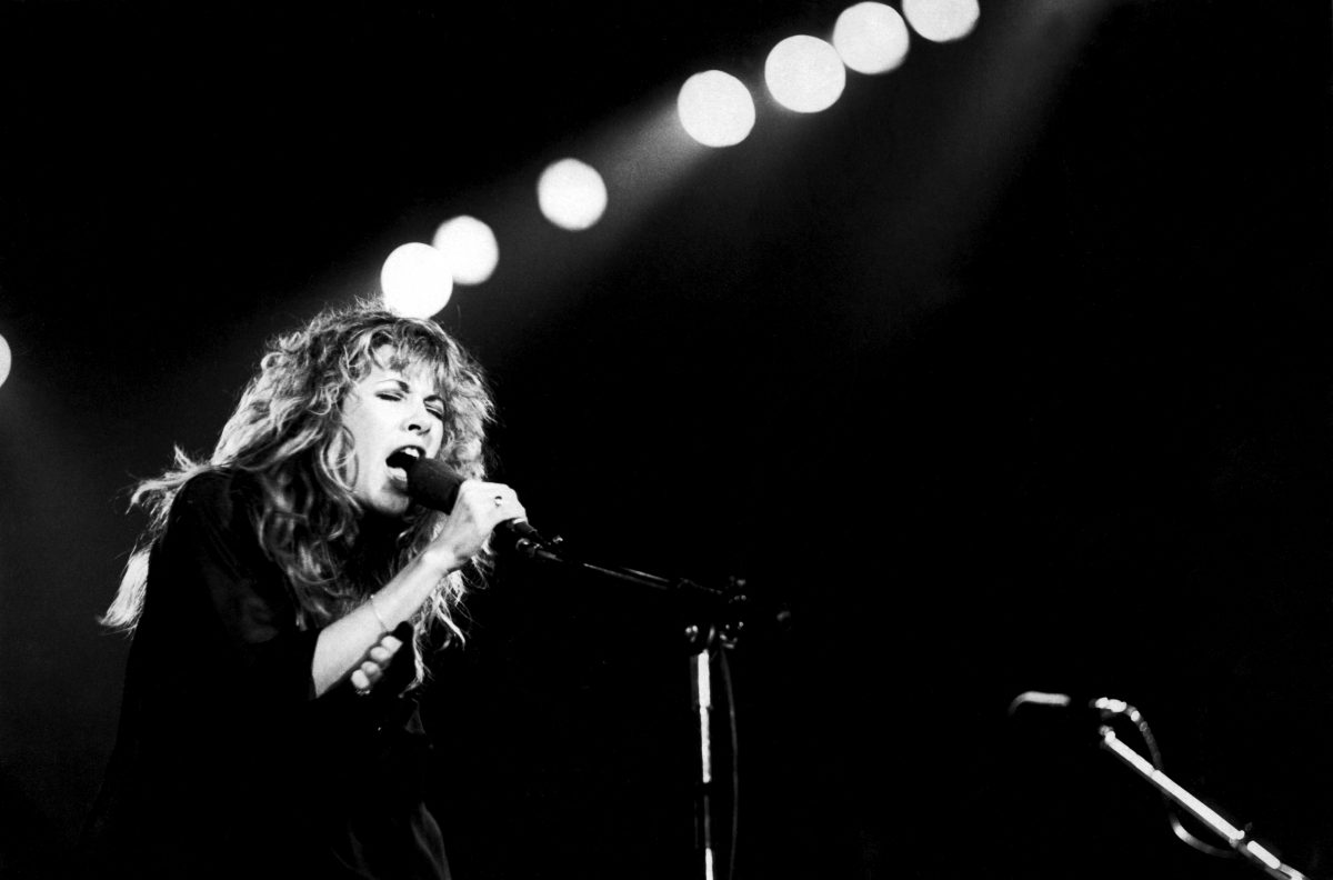 A black and white photo of Stevie Nicks singing into a microphone.