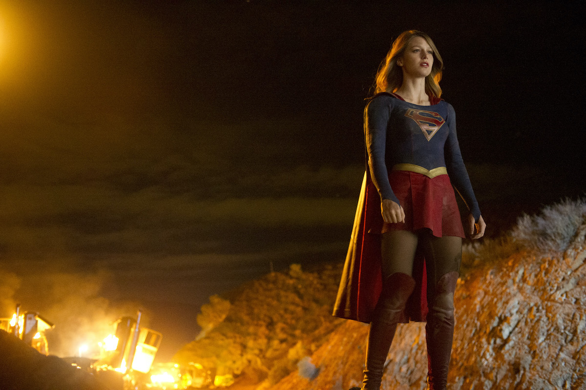 Kara Danvers in the Supergirl suit in front of a fire