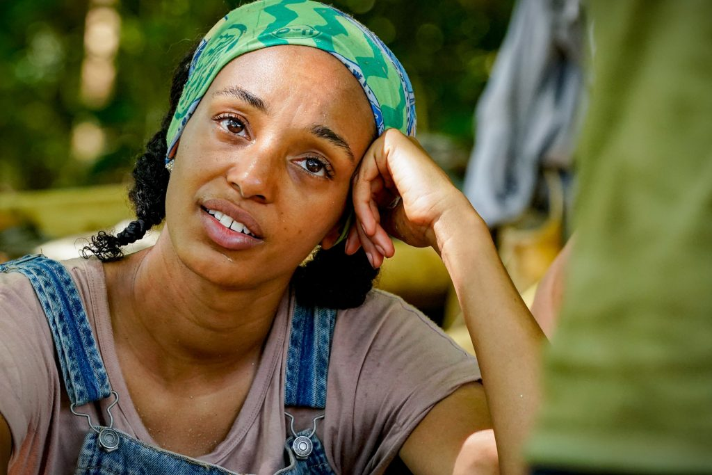 Shantel Smith on 'Survivor 41' wears a shirt and overalls as she sits down on the ground.