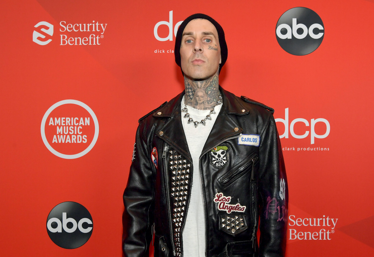 Travis Barker in front of a red background