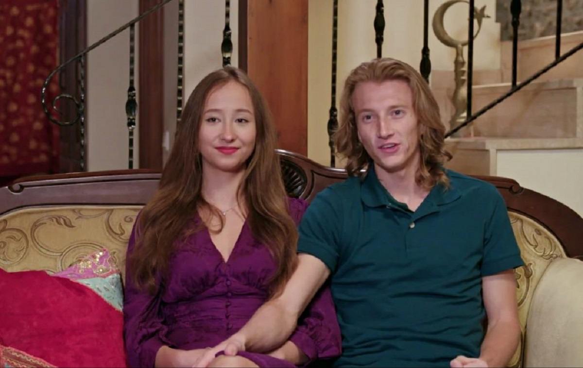 Alina and Steven in '90 Day Fiancé: The Other Way '- Alina wears a purple dress, Steven a green polo shirt.  They are sitting on a sofa facing the camera.  Steven has his hand on his knee.