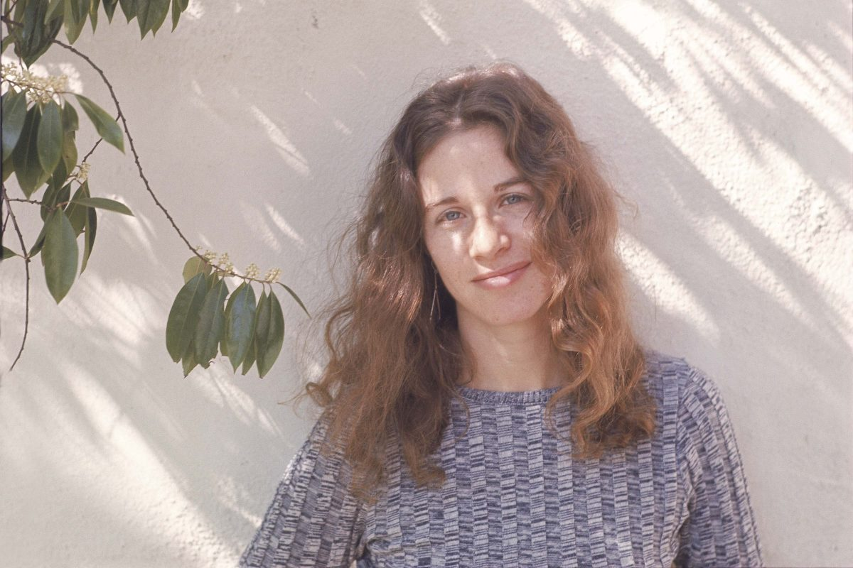 Carole King leaning on a wall near a plant