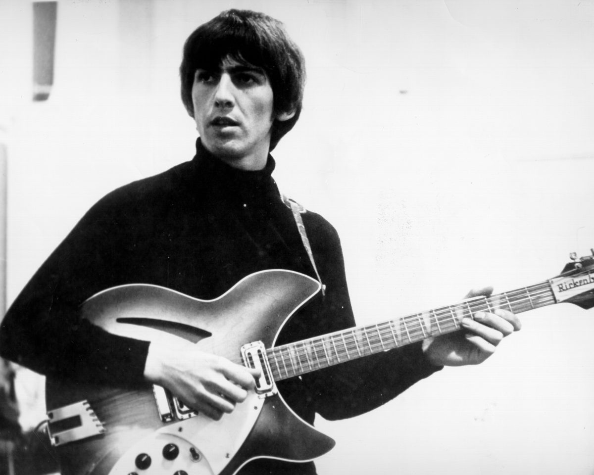 George Harrison playing songs on his guitar