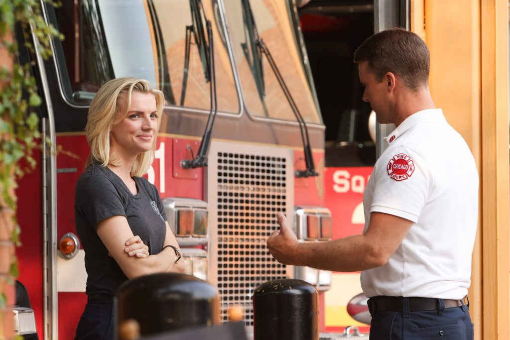 Kara Killmer and Jesse Spencer stand in front of the firehouse on Chicago Fire.