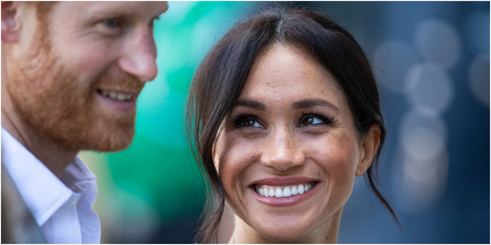 Prince Harry and Meghan Markle pose for a paparazzi photo.