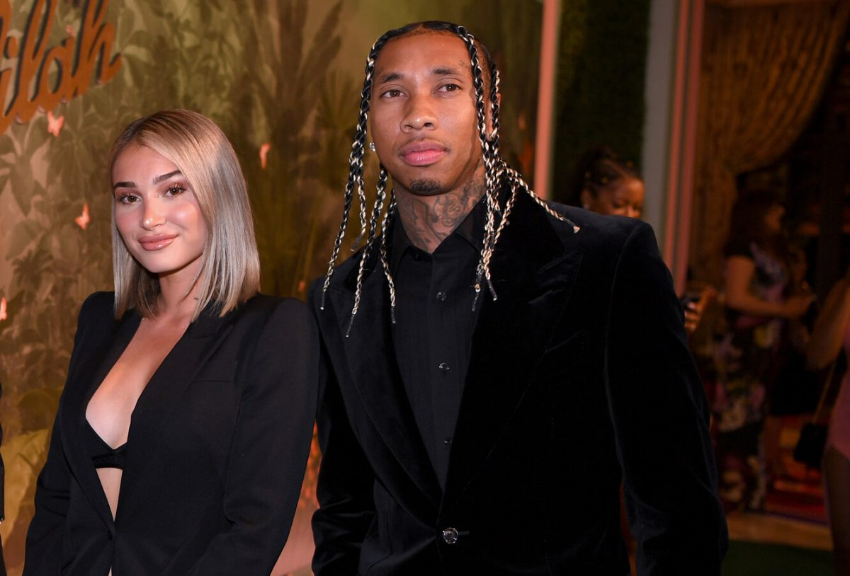 Camaryn Swanson smiling and wearing a black jacket stands next to Tyga, wearing a black jacket and black shirt.