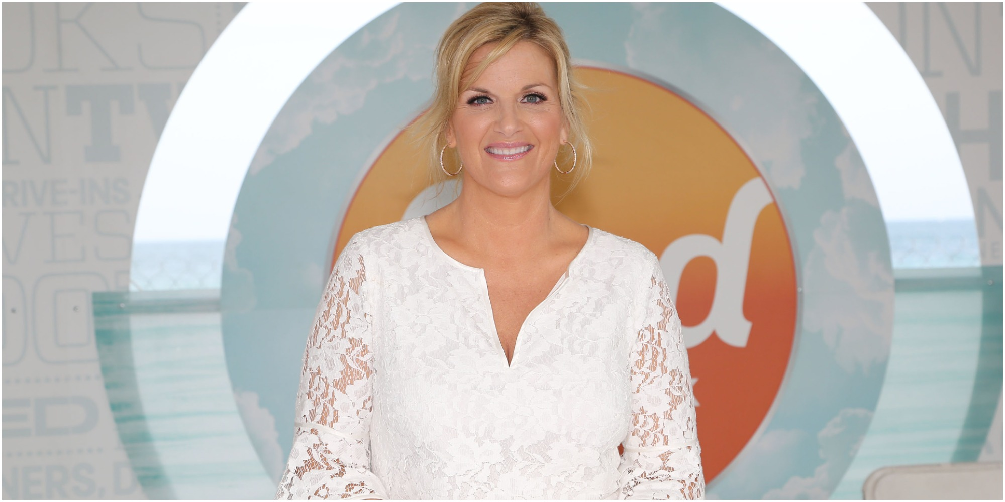 Trisha Yearwood poses in front of the Food Network logo.